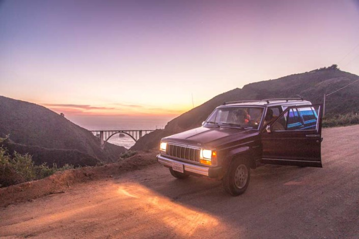 Jeep Cherokee near Bixby Bridge at sunset.